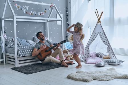 Plezier samen. Jonge vader gitaar spelen voor zijn dochtertje en glimlachen terwijl de uitgaven vrije tijd thuis