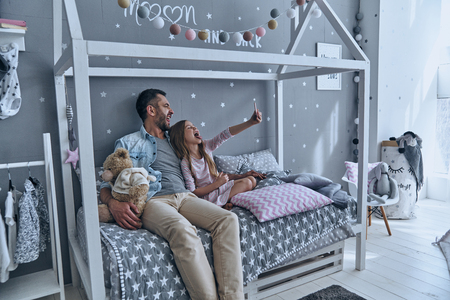 Going crazy together. Young father and his little daughter taking selfie while sitting on the bed at home photo