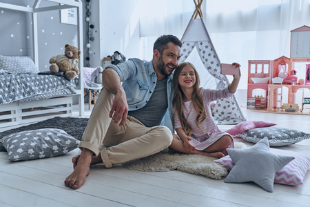 Selfie with dad. Young father and his little daughter taking selfie while sitting on the floor in bedroom with the tent in the background photo