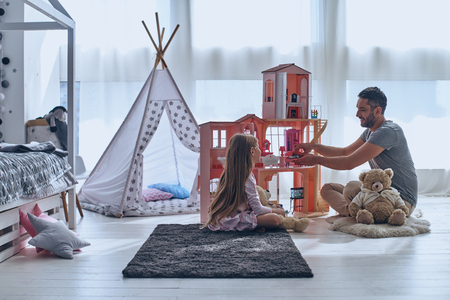 Using imagination. Father and daughter playing with a dollhouse together while sitting on the floor in bedroom Stock Photo