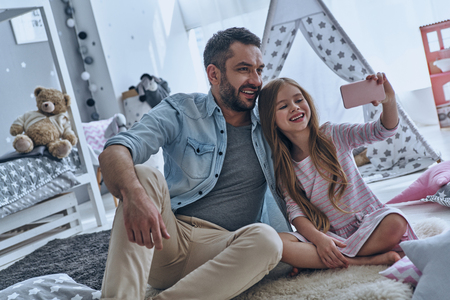 Selfie time! Cheerful father and his little daughter taking selfie while sitting on the floor in bedroom with the tent in the background photo