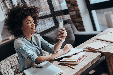the place is important: Answering important messages. Beautiful young African woman looking at smart phone and smiling while sitting at her working place in restaurant Stock Photo