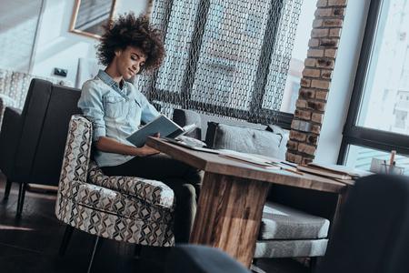persona leyendo: Participación en la lectura. Joven y bella mujer africana leyendo un libro mientras estaba sentado en un café o oficina creativa