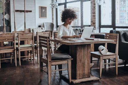 usando computadora: Trabajando en un nuevo proyecto. mujer africana joven hermosa en ropa de sport elegante que trabaja con ordenador mientras está sentado en el café Foto de archivo