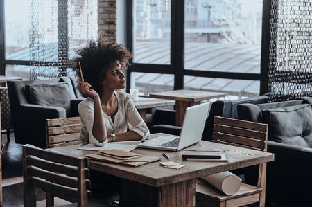 Tomando algo de tiempo para pensar. Reflexiva mujer africana joven sosteniendo un lápiz y parece ausente mientras que se sienta en café photo