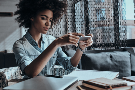 Taking one more shot. Thoughtful young African woman holding a smart phone and looking at it while sitting in cafe or creative office photo