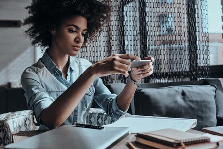 Tomando una oportunidad más. Reflexiva joven africana que sostiene un teléfono inteligente y mirarlo mientras se está sentado en el café o en la oficina creativa photo