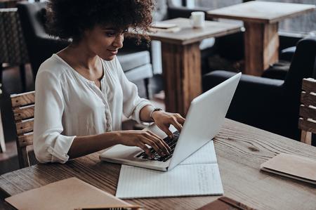 Het ontwikkelen van nieuwe project. Mooie jonge Afrikaanse vrouw met behulp van computer en lachend zittend in cafe