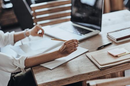 ajetreado día de trabajo. Primer plano de la mujer africana que trabaja con su cuaderno de notas y un ordenador portátil mientras está sentado en el restaurante photo