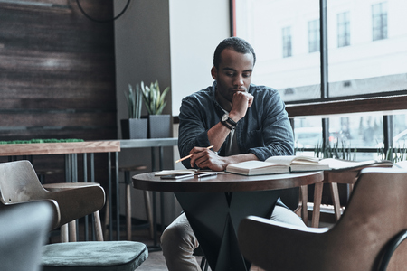 Gathering relevant information. Thoughtful young man keeping hand on chin and looking at the book while sitting at his working place in the cafeteria Stock Photo