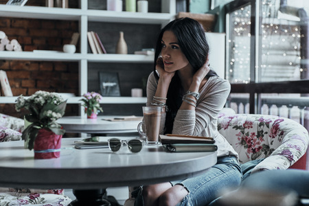 Beautiful daydreamer. Attractive young woman looking away with a smile while sitting in restaurant