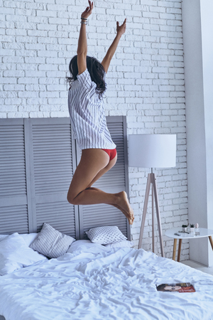 Enjoying good morning. Full length of playful young woman keeping arms raised while jumping on the bed Reklamní fotografie - 79127909