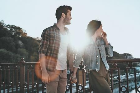 Match parfait. Beau jeune couple tenant la main et détournant les yeux tout en restant debout sur le pont extérieur Banque d'images