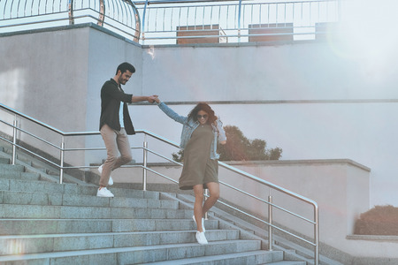 She is everything to him. Full length of handsome man and young attractive woman holding hands while walking down the stairs outdoors Stock Photo