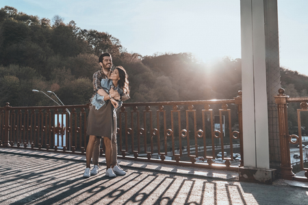 Happy to be together. Full length of beautiful handsome man embracing young attractive woman while standing on the bridge outdoors Stock Photo