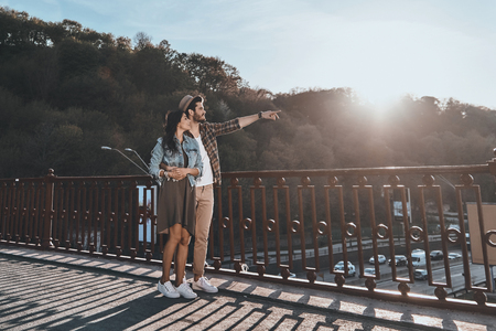 Love inspires them. Full length of handsome man embracing young attractive woman and pointing away while standing on the bridge outdoors