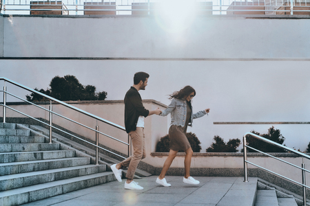 He will never let her go. Full length of handsome man and young attractive woman holding hands while walking down the stairs outdoors Stock Photo