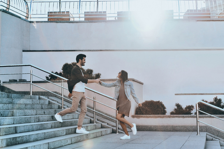Going crazy together. Full length of handsome man and young attractive woman holding hands while walking down the stairs outdoors