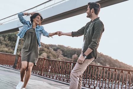 living moment: Living this moment. Beautiful young couple holding hands and spinning while dancing on the bridge outdoors Stock Photo