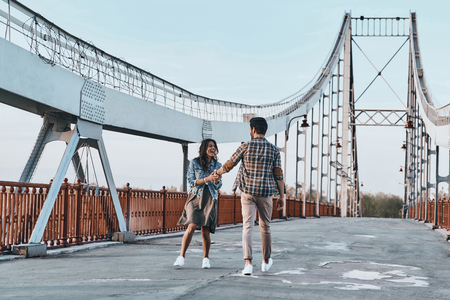Just having fun. Full length of playful young couple holding hands while walking on the bridge outdoors