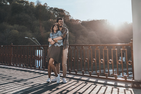 I will keep you warm! Full length of handsome man embracing young attractive woman while standing on the bridge outdoors