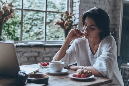 only adult: Enjoying nice breakfast. Beautiful young woman eating enjoying her breakfast at home