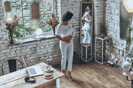 スキニー ジーンズにフィットします。彼女のジーンズを履き、鏡で見て魅力的な若い女性の完全な長さ