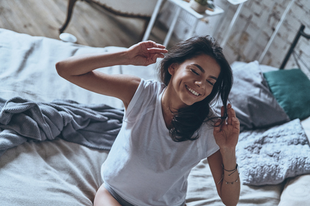 Feeling happy and refreshed. Top view of beautiful young woman stretching and smiling while sitting on the bed at home