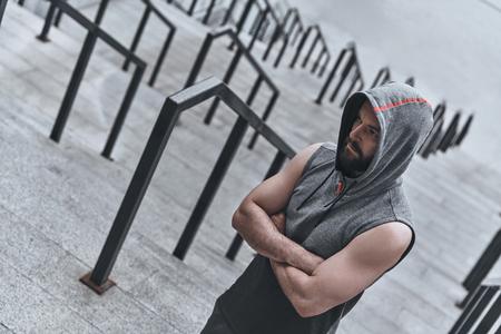 自信を持って。外階段に立っている間、腕組みを維持するスポーツ衣料でハンサムな若い男