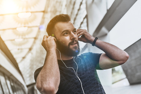 Music is his motivation. Handsome young man in sport clothing adjusting his headphones and looking away while standing outside Stok Fotoğraf