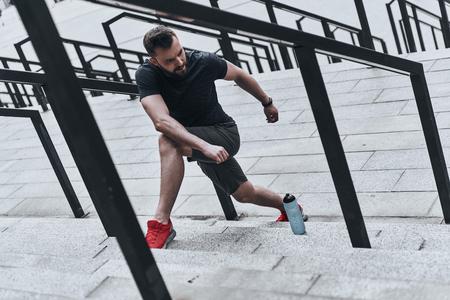 ストレッチ体操。スポーツ衣料品外運動をしながら離れて見てでハンサムな若い男