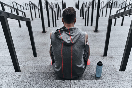 Tired after workout. Rear view of young man in sport clothing sitting on the stairs while spending time outside