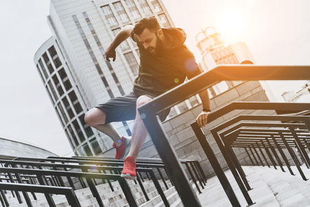 Sport is the way of his life. Low angle view of handsome young man in sport clothing jumping over railing while exercising outside