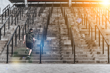 Achieving best results. Full length rear view of young man in sport clothing running up the stairs while exercising outside Stock fotó