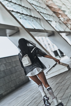 Free to go anywhere. Full length rear view of young woman in casual wear skating outdoors