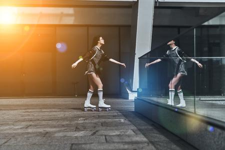 ストリート ・ ファッション。カジュアルで魅力的な若い女性の完全な長さを屋外で時間を過ごしながらスケート着用します。 写真素材