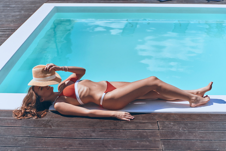 Caching a tan. Full length top view of beautiful young woman in swimwear covering face with hat while sunbathing by the pool