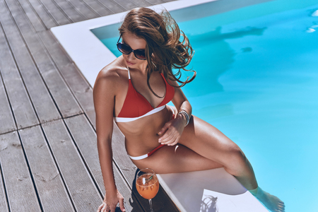 Beauty by the pool. Attractive young woman in swimwear looking away while sitting by the pool outdoors