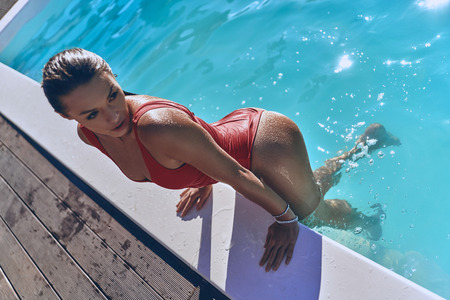 Top view of attractive young woman in swimwear looking away while getting out the swimming pool