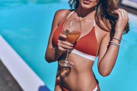 Total relaxation. Close up of young woman in swimwear holding a glass and touching hair with hand while standing by the pool outdoors Banque d'images