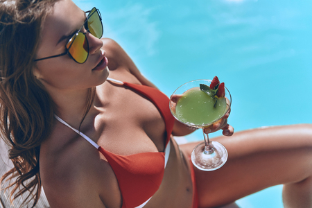 Effortless beauty. Top view of attractive young woman in swimwear holding a glass while sitting by the pool outdoors