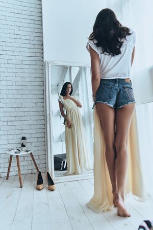 素晴らしいドレス!自宅の鏡で見ながら彼女のドレスにしようとして魅力的な若い女性の完全な長さのリアビュー