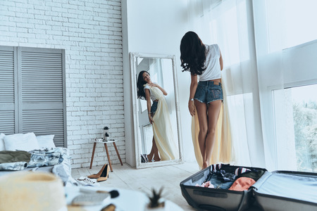 This dress is perfect! Full length rear view of attractive young woman trying on her dress while looking in the mirror at home
