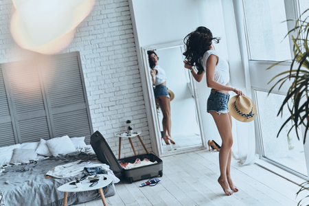 Happy about summer vacation. Full length of beautiful young woman holding sun hat while looking in the mirror at home Stock Photo - 81841380