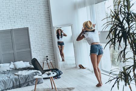 彼女は、すべてのファッションについてです。彼女の太陽の帽子を試着しながら鏡を見て若い女性の完全な長さ背面図