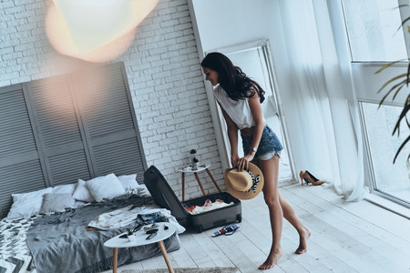 Getting ready for summer vacation. Full length of beautiful young woman holding sun hat while walking in the bedroom Stock Photo - 81841879