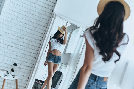 Ready for summer vacations. Rear view of attractive young woman trying on her sun hat and smiling while standing in front of the mirror at home
