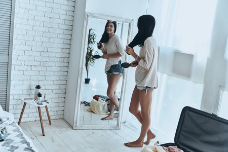Totally ready. Full length of attractive young woman combining her hair and smiling while standing near the mirror at home