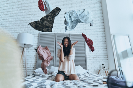 Too hard to choose! Beautiful young woman sitting on bed and making face while clothing flying everywhere