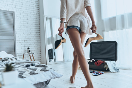 Preparing to vacation. Close up rear view of attractive young woman walking through the bedroom while packing at home Stock Photo - 81841763